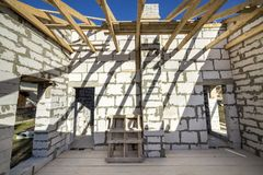 House interior under construction and renovation. Energy saving walls of hollow foam insulation blocks and bricks, ceiling beams. And roof frame royalty free stock photo