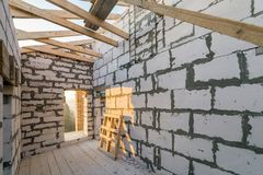 House interior under construction and renovation. Energy saving walls of hollow foam insulation blocks and bricks, ceiling beams. And roof frame royalty free stock image