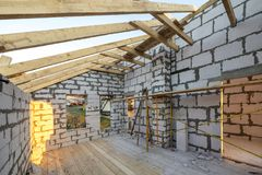 House interior under construction and renovation. Energy saving walls of hollow foam insulation blocks and bricks, ceiling beams. And roof frame stock image