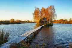 House on the island. Bridge on a river to a picturesque hut Royalty Free Stock Image