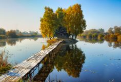 House on the island. Bridge on a river to a picturesque hut Royalty Free Stock Photos