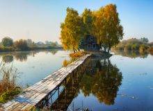 House on the island. Bridge on a river to a picturesque hut Royalty Free Stock Photo