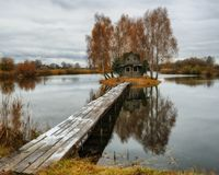House on the island. Bridge on a river to a picturesque hut Stock Photography