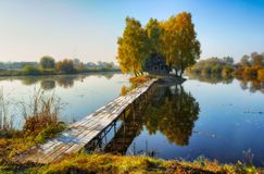 House on the island. Bridge on a river to a picturesque hut Stock Image