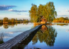 House on the island. Bridge on a river to a picturesque hut Stock Photos