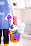 House keeper with cleaning equipment in bucket. House keeper with apron and rubber gloves holding basket full of cleaning supplies and equipment in front of royalty free stock image