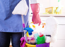 House keeper with cleaning equipment in bucket. House keeper with apron and safety gloves holding basket full of cleaning supplies and equipment in front of royalty free stock image