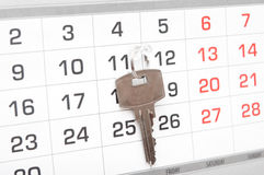 A house key on a calendar background Royalty Free Stock Photos