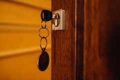 House key in the door. Key with key chain opens or closes the wooden door. royalty free stock photos