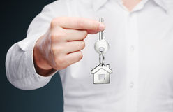 House key in hand. House key with house shaped keychain Royalty Free Stock Images