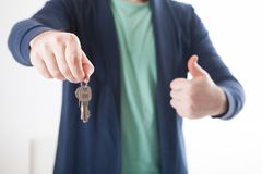 House key in hand. Bright picture of man hand holding house keys. Holding a thumb up Royalty Free Stock Photos