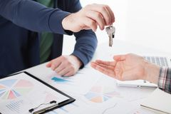 House key in hand. Young business man giving house with keys of customer at agency office Stock Image