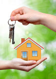 The house with key in the hands. On green background Royalty Free Stock Image