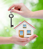 The house with key in hands. On green background Royalty Free Stock Photos