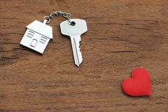 House key with home keyring decorated with mini red heart on wood texture background, sweet home concept. Copy space stock images