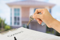House key. Homeowners showing house keys in front of a new home with documents contract. Housing purchase and insurance concept Royalty Free Stock Images