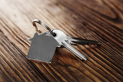 House key on house shaped keychain on wooden floorboards Stock Photos