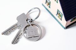 House key on a house shaped pendant. Real estate agent concept on white background stock photography