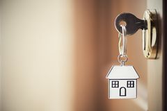 House key in the door. House key on a house shaped silver keyring in the lock of a door Stock Photography