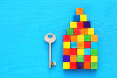 House key and house shaped from wooden colorful blocks blue textured background. concept for real estate, moving home or renting p royalty free stock photography