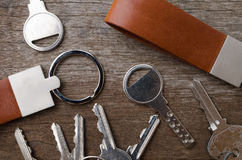 House key with leather key chain on wooden background Royalty Free Stock Image