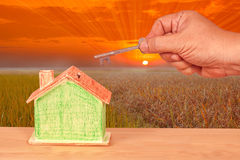 House key with a miniature model house on landscape Royalty Free Stock Image