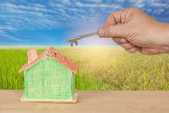 House key with a miniature model house on landscape Stock Photography