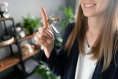 House key rotates on the finger in womans hands. Young pretty woman smiles. Modern light lobby interior. Real estate stock photography