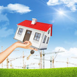 House and key in womans hand with building cranes Royalty Free Stock Photography