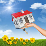 House and key in womans hand with flowers Stock Image
