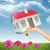 House and key in womans hand with pink flowers Stock Photography