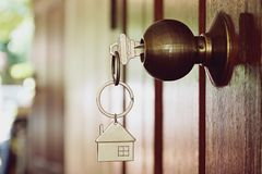 House key in wooden front door. House key in the wooden front door in the morning Royalty Free Stock Images