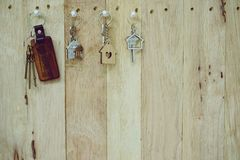 House key with wooden home keyring hanging on wood board background, property concept, copy space. House key with wooden home keyring hanging on wood board stock images