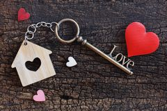 House keyring and love shape key on vintage wooden table. Decorated with mini heart as sweet gift for lover or family member. Home. Sweet home concept. Copy stock photo