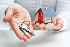 House and keys. Real estate agent with house model and keys Stock Photography
