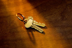 House keys. Brass house keys in sunlight on a wood background Stock Image
