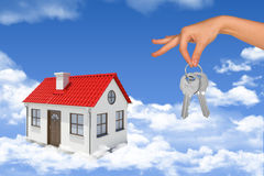 House with keys in clouds. House with hand holding keys in blue sky with clouds Stock Images