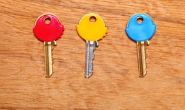 House keys with colorful plastic coats caps on table Royalty Free Stock Images