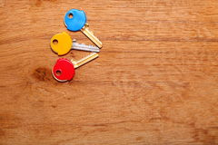 House keys with colorful plastic coats caps on table Royalty Free Stock Photos