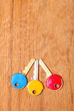 House keys with colorful plastic coats caps on table Stock Images