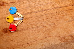 House keys with colorful plastic coats caps on table Royalty Free Stock Photography