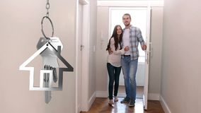 House keys and key fob hanging with couple in new home in the background