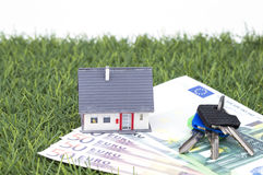 House Keys and money. Little house with money and bunch of keys on grass royalty free stock photo
