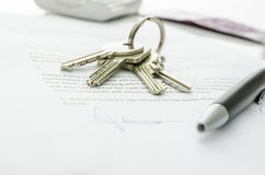 House keys on a contract of house sale. House keys and money on a signed contract of house sale.  Focus on keys Royalty Free Stock Image