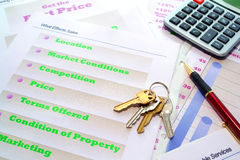 House Keys on Real Estate Marketing Portfolio. Set of house keys and calculator on real estate agent marketing plan binder with loose demonstration pages during Royalty Free Stock Photography