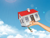 House and keys in womans left hand under clouds Stock Images
