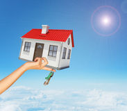 House and keys in womans right hand under clouds Stock Photo