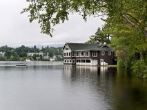House in the Lake. Beautiful boat house located on the calm water of a lake, hidden behind some trees Royalty Free Stock Photography