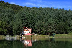 House by the lake. House built on lake shore on forest and blue sky background Stock Photos