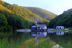 House on the lake. A lake in Romania with reflection of a house and trees in the water. Scenic view of hills in the back of the house at sunset Stock Image